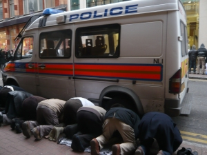 Moments from the action, a group of men kneel down to pray, behind the cover of a Metropolitan police van